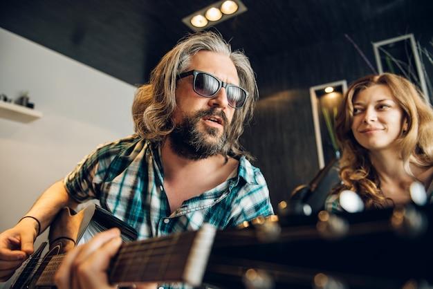 Любящий мужчина играет на гитаре для своей женщины