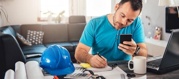 Человек пишет заметки и держит смартфон