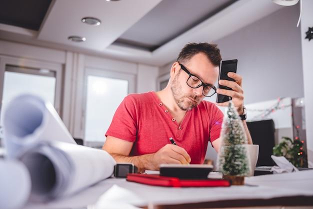 メモを書くと、スマートフォンを保持している男