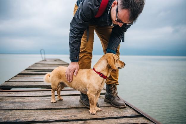 ドックに立っている彼の犬を持つ男