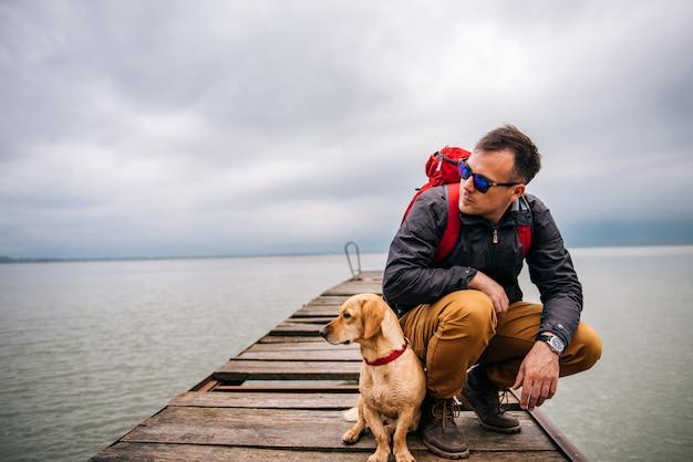 ドックに座っている彼の犬を持つ男