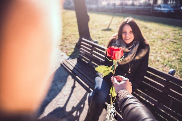 女性に赤いバラを与える男