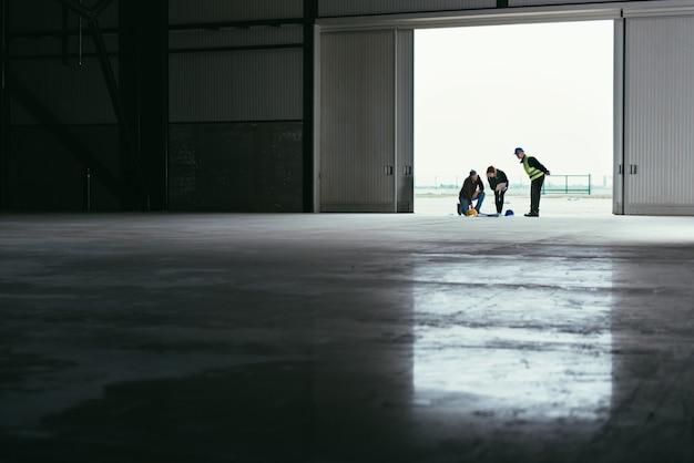建築家チームが作業現場で青写真を読む