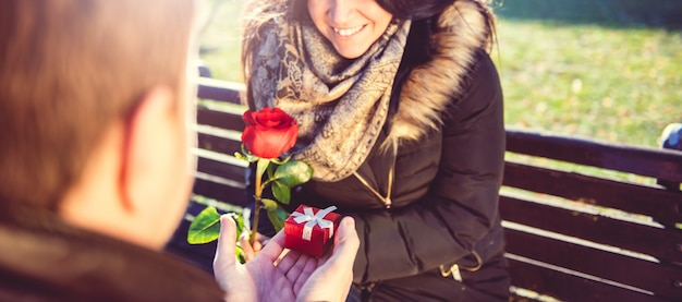 男はささやかな贈り物を持つ女性を驚かせる
