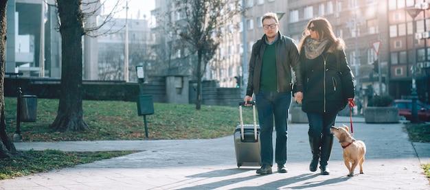 カップルはスーツケースと犬の散歩