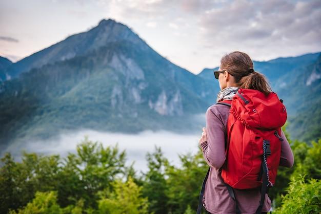 山でのハイキングと日の出を見て女性