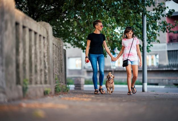 Мать и дочь гуляют на улице с собакой