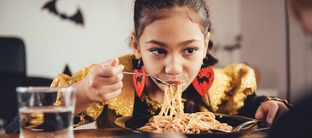 Маленькая девочка ест спагетти