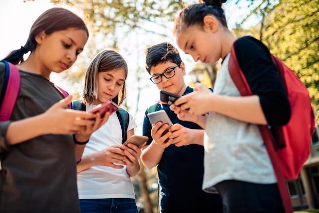 学校の子供たちのグループがたむろして、スマートフォンを使用して