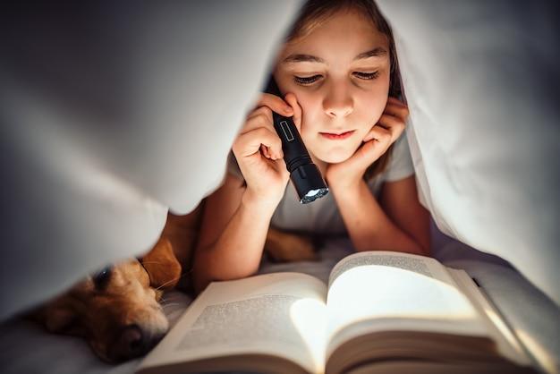 夜遅くに本を読んで毛布の下で彼女の犬と一緒にベッドに横たわっている少女