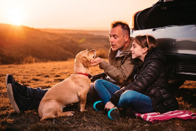 Отец и дочь гладят собаку на кемпинге на холме