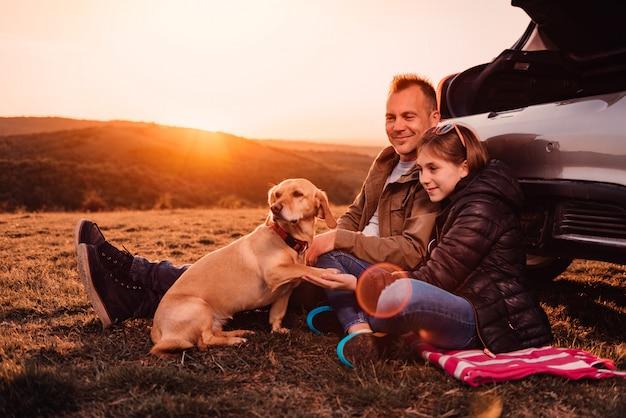 Собака дает лапу своим владельцам в поход на холме