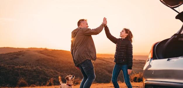 丘でのキャンプでハイタッチを与える父と娘