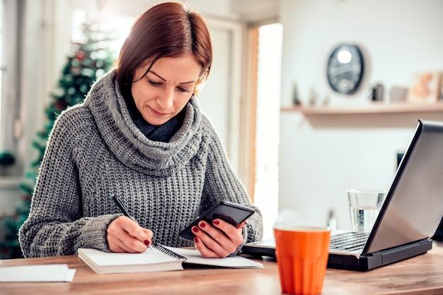 女性がスマートフォンを押しながら彼女のノートにメモを書く