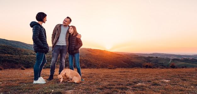 丘の上に立っている間を受け入れる犬と家族