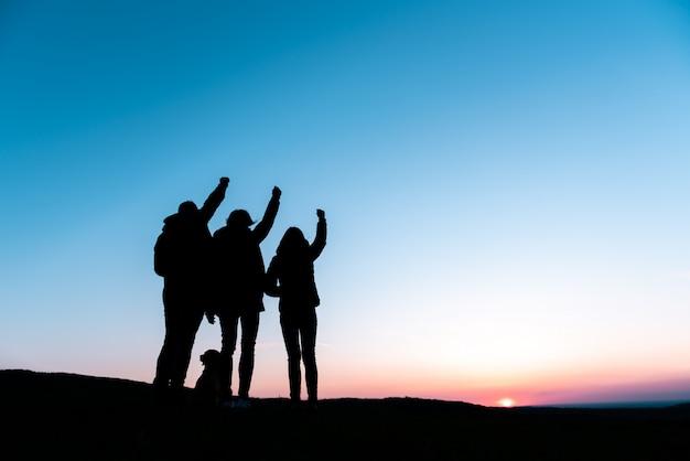 腕を上げると丘に立っている犬と家族