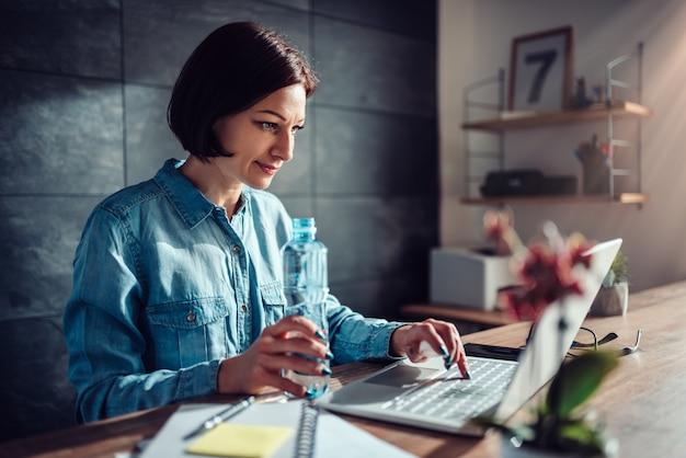 Женщина, используя ноутбук в офисе и держа бутылку воды