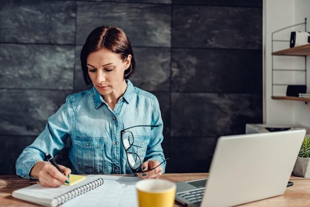 オフィスでメモ帳にメモを書く女性