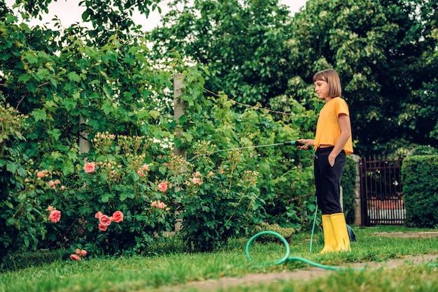 Девушка поливает цветы в саду