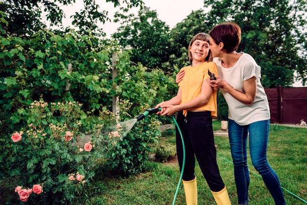 Мать и дочь работают вместе в саду