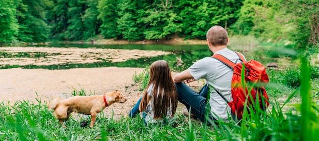 Отец и дочь у озера с собакой