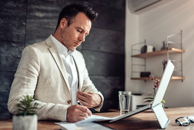 レポートデータを分析し、メモを書くビジネスマン