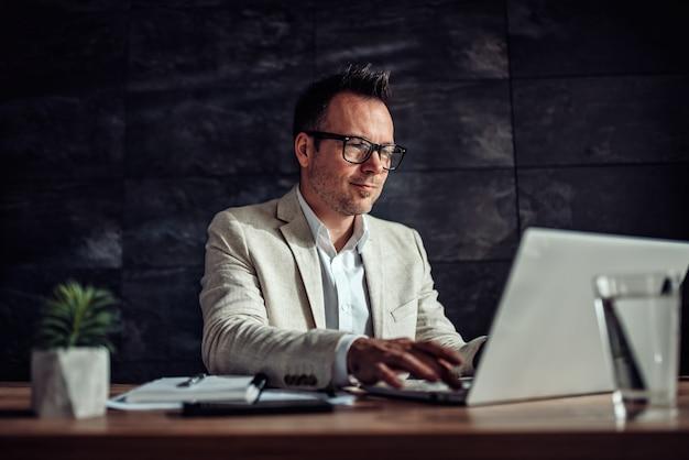 彼の机に座って、オフィスでラップトップを使用しての実業家