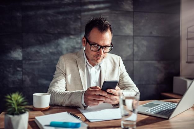 彼の机に座って、スマートフォンを使用しての実業家