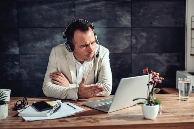 彼のオフィスでオンライン会議を持つ実業家