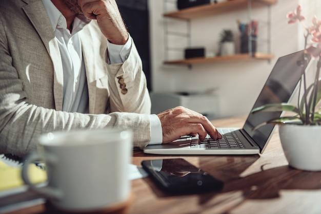 Бизнесмен сидел на своем столе и используя ноутбук в офисе