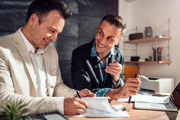 Клиент подписывает договор в офисе агента по недвижимости