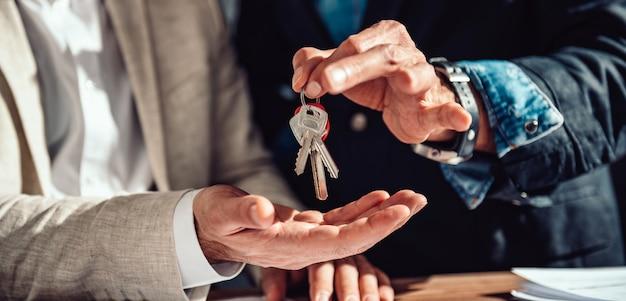 Агент по недвижимости передает клиенту ключи от квартиры