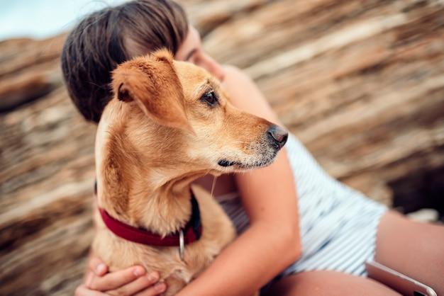 彼女の犬を抱きしめる少女