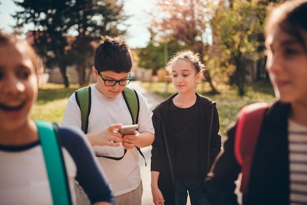 Мальчик идет в школу с одноклассниками и с помощью смартфона на школьном дворе