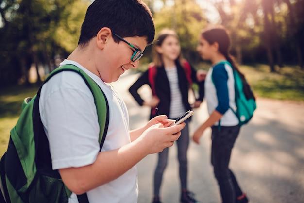 Мальчик с помощью смарт-телефона на школьном дворе