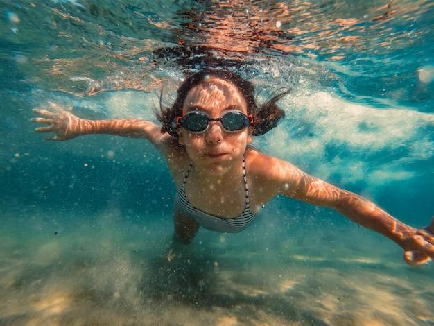 海で泳いでいる少女の水中写真