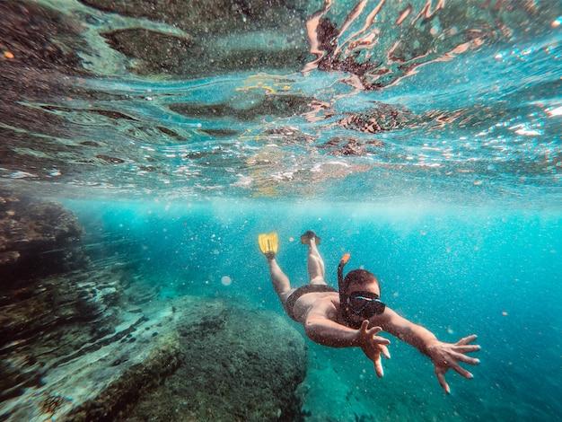 Подводная фотография мужчины, ныряющего с маской и трубкой в море