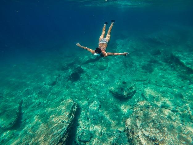 浅い海の水に飛び込む女性
