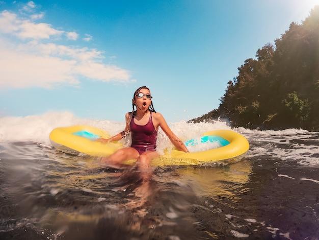 エアベッドで海で遊ぶ女の子