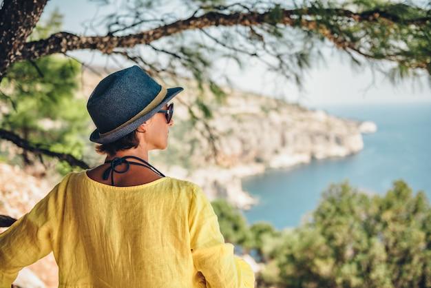 ツリーの下の崖の上に立って、海を探している女性