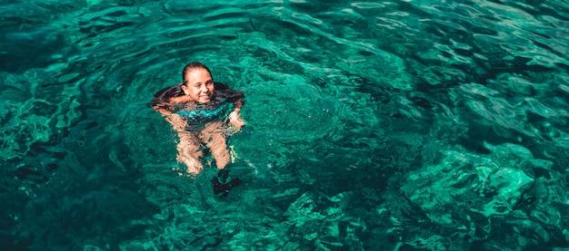 笑顔で海で泳いでいる少女