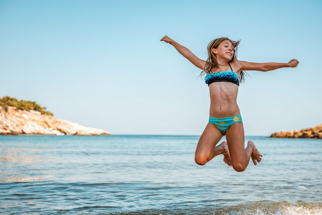 海沿いのビーチでジャンプの女の子