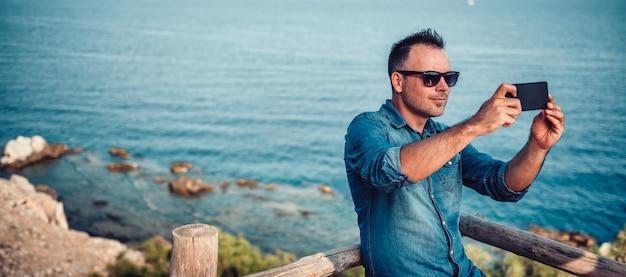 海沿いのスマートフォンで写真を撮る男性