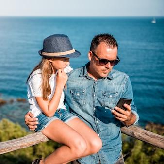 父と娘がスマートフォンを使用して海で木製のフェンスにもたれる