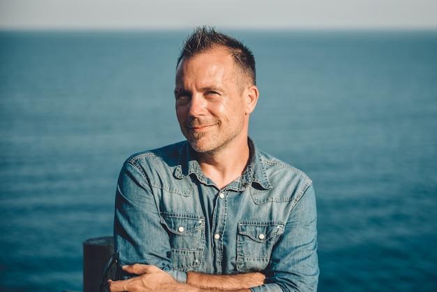 海のそばに立っているデニムシャツを着ている男性