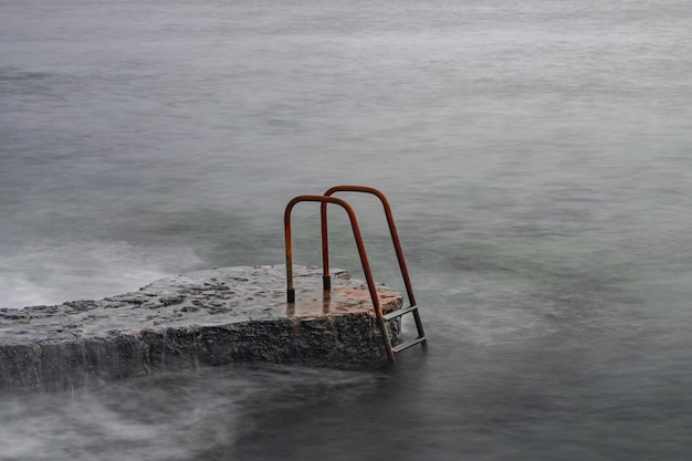 大西洋の錆びた金属製のはしご、長時間露光写真、夜の光、ラカレタ、エルイエロ、カナリア諸島、スペイン