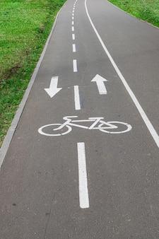 アスファルト道路に白く塗られた自転車レーン信号