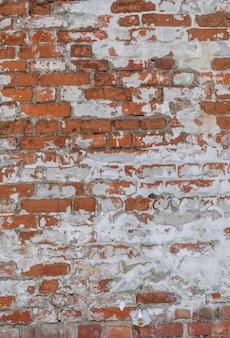 雪でオレンジ色の風化したレンガの壁