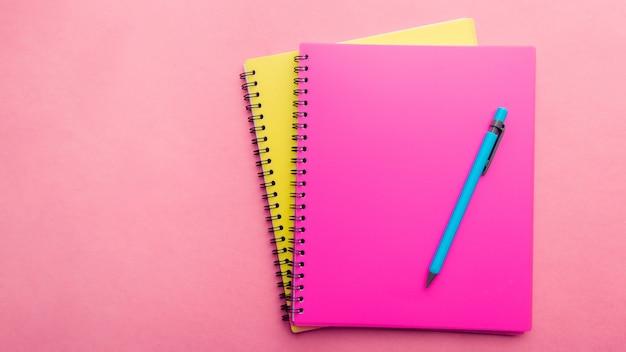 Два блокнота розовый и желтый с синей ручкой на розовом фоне. место для текста. примечание лист