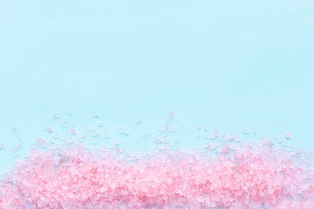 Куча крупных посыпанных кристаллов розовой морской соли крупным планом на синем